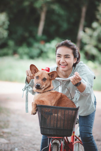Cheerful girl with dog in basket of bicycle standing outdoors