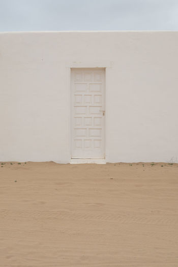 White door and wall  on sand desert landscape