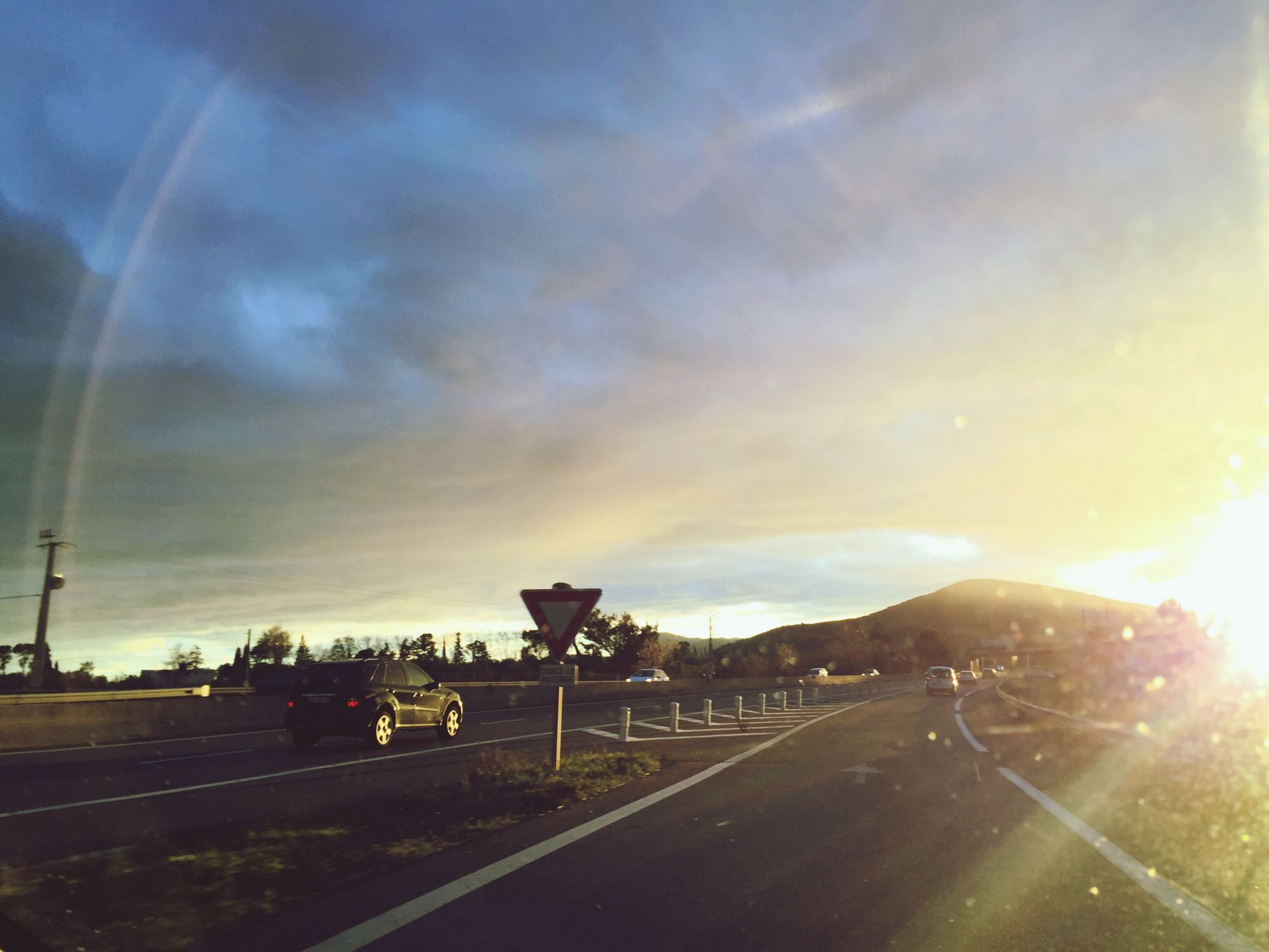 transportation, sky, car, road, land vehicle, cloud - sky, mode of transport, sunset, street, cloudy, cloud, the way forward, sunbeam, road marking, on the move, outdoors, nature, sun, sunlight, weather