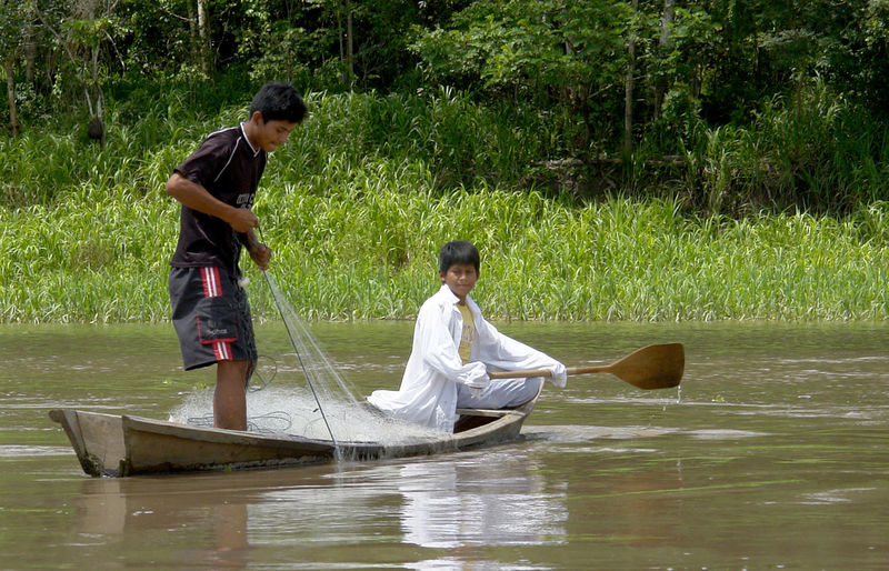 Side view of two men in boat on lake