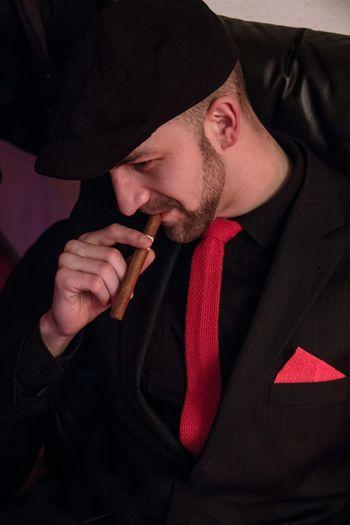 Close-Up Of Man Smoking Cigar While Sitting On Sofa At Home
