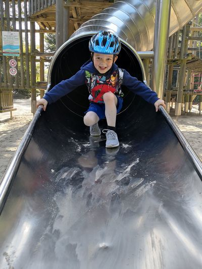 Full length of boy on slide at playground