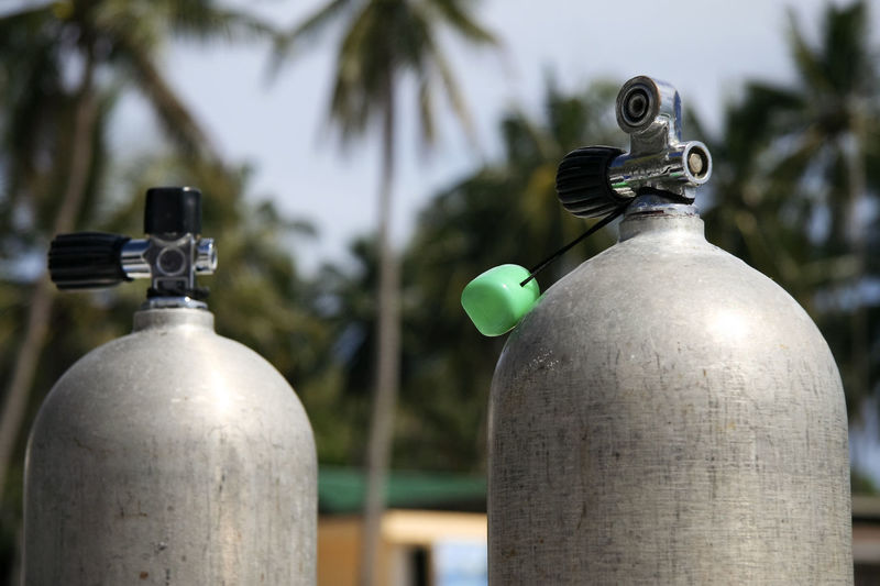 Close-up of cylinders against trees