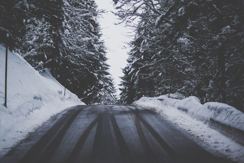Snow covered road passing through forest