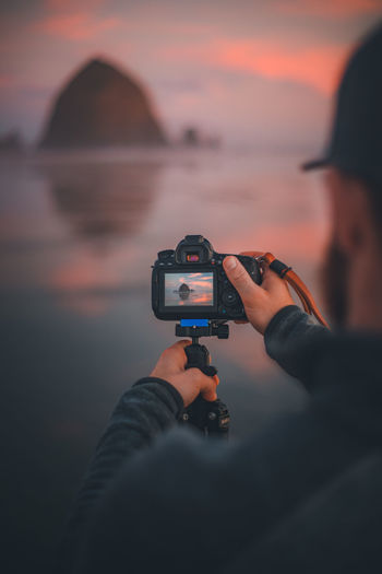 Man photographing camera against sky during sunset