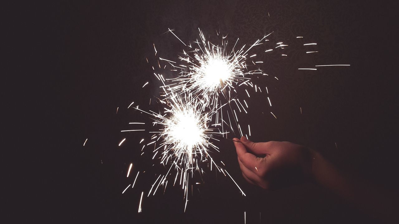 sparks, human hand, sparkler, firework - man made object, long exposure, one person, celebration, holding, motion, real people, burning, night, illuminated, firework display, close-up, arts culture and entertainment, human body part, lifestyles, indoors, firework, people