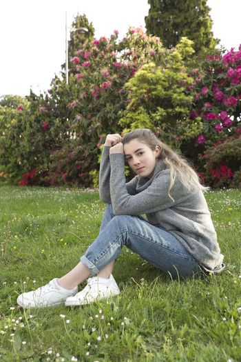 16 year old teenager sitting in a park with grass and flowers, taken in Limoges, France. 16 Years Spanish Woman Adolescent Beautiful Woman Casual Clothing Contemplation Day Flower Flowering Plant Grass Leisure Activity Lifestyles Looking At Camera Nature One Person person Plant Portrait Relaxation Smiling Teen Teenager Teenagers Only Young Women