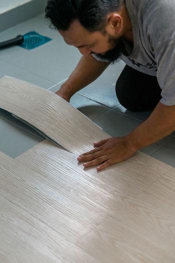 Man cutting hardwood floor
