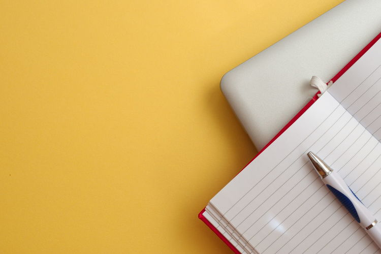 Technology Notebook Still Life Copy Space Indoors  Pen Paper Yellow No People High Angle View Table Note Pad Office Supply Pencil Writing Instrument Close-up Office Blank Laptop Directly Above Isolated Colored Background Copy Space Indoors  Document Office