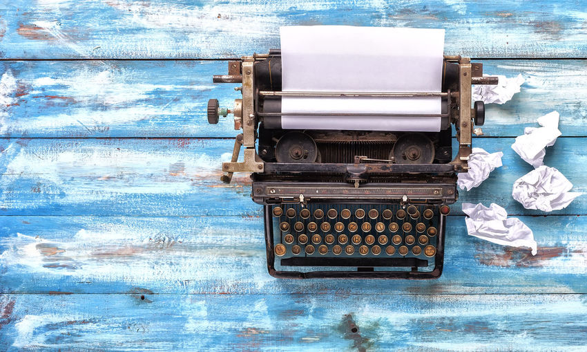 Directly above shot of old typewriter with crumpled papers on table