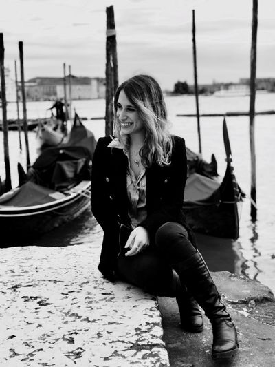 Smiling woman sitting against canal