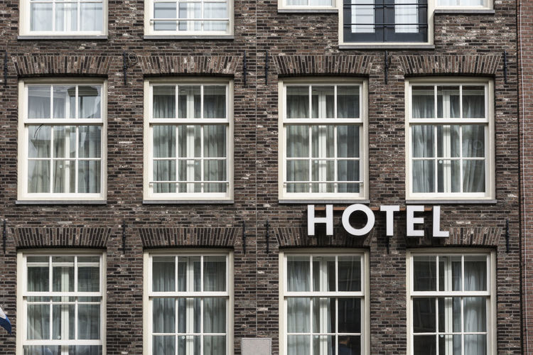 Hotel sign in exterior view on a brick wall Classic Façade Holiday Retro Room Service Sign Signage Text Travel Vacations Wall Word Accommodation Apartment Architecture Brick Building Exterior Detail Hotel Luxury Motel Pattern Symbol Urban