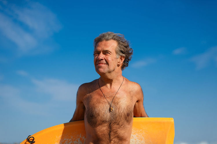 Close-up of shirtless man against blue sky