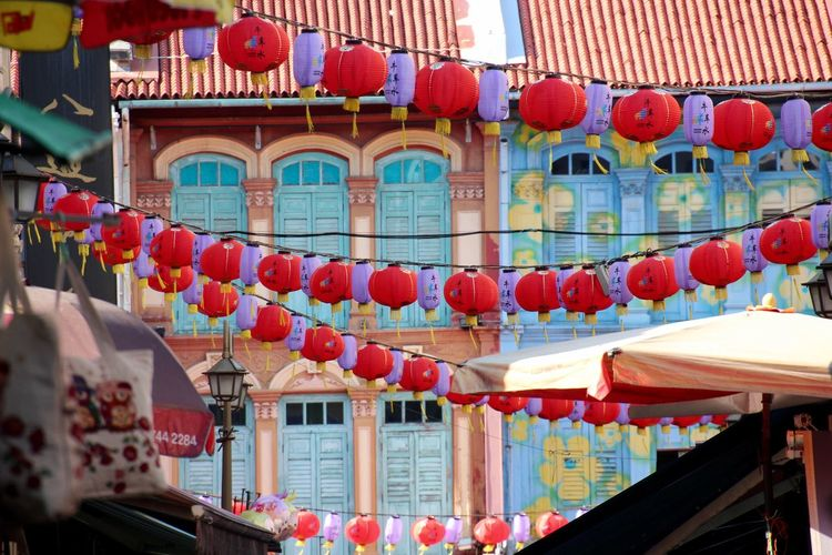 Low angle view of chinese lanterns hanging against building during new year