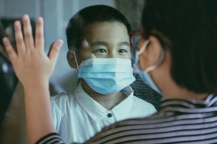 Cute boy wearing mask looking at sibling