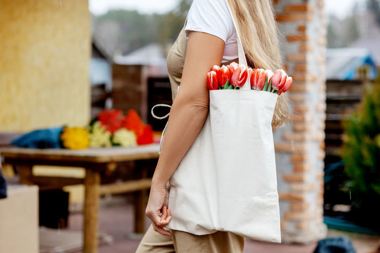 Close-up of a bouquet of tulips in a cloth bag on the shoulder of a girl. gift for women's day