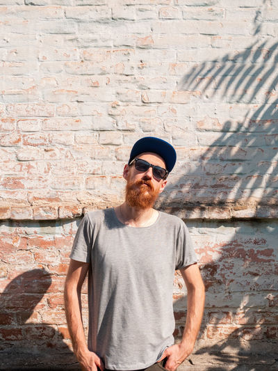 Handsome hipster man with lush beard and mustache on light brick wall background palm leaves shadow.