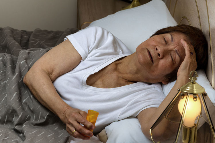 High Angle View Of Senior Woman Holding Medicine Bottle While Sleeping On Bed At Home