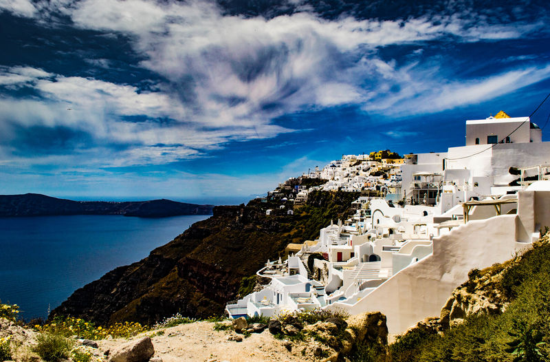 Buildings On Cliff By Sea Against Sky At Santorini