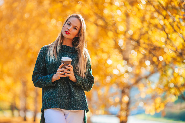 Young woman using smart phone during autumn