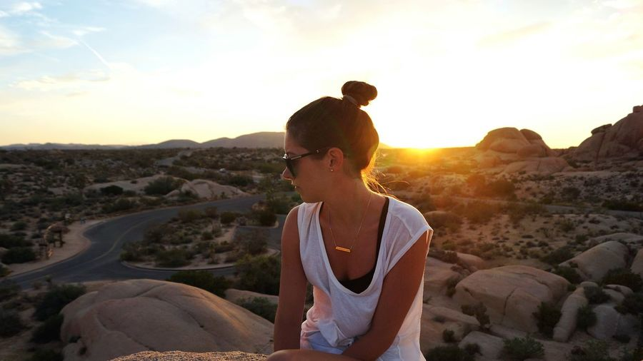 Young woman sitting on cliff at joshua tree national park