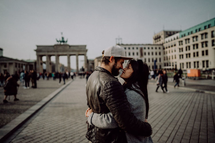 Side view of couple romancing while standing on street in city