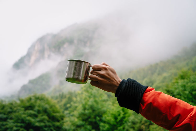 Midsection of person holding drinking cup against foggy mountains