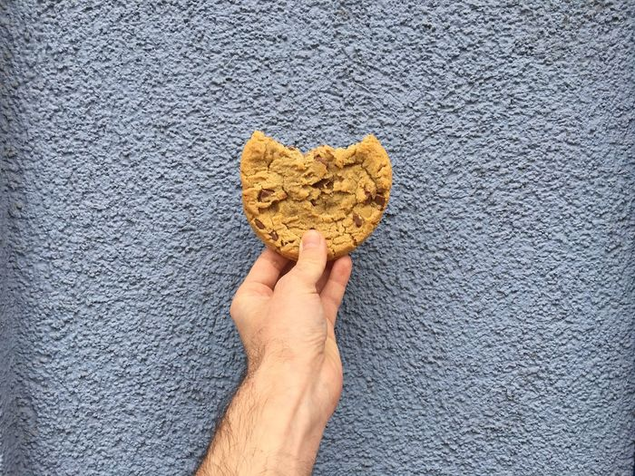 Cropped Image Of Man Holding Cookie Against Wall