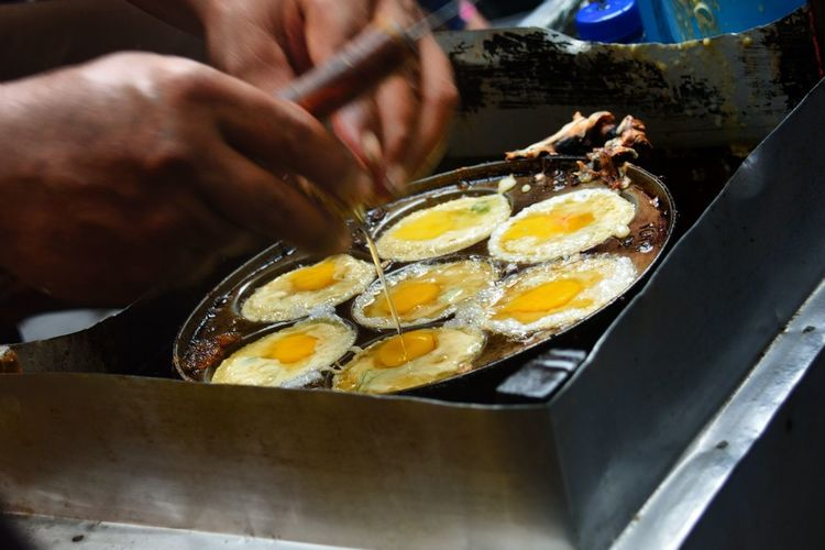 Cropped Image Of Man Boiling Eggs On Stove