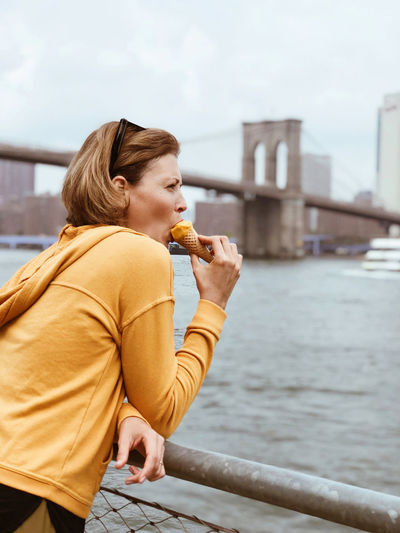 Tourist woman eating  cone of sorbet against background of manhattan city and brooklyn bridge.