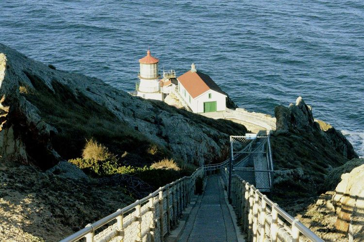 High Angle View Of Pier Leading Towards Lighthouse By Sea