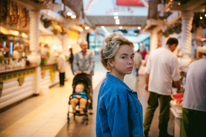 Portrait Of Young Woman Standing In Illuminated Market