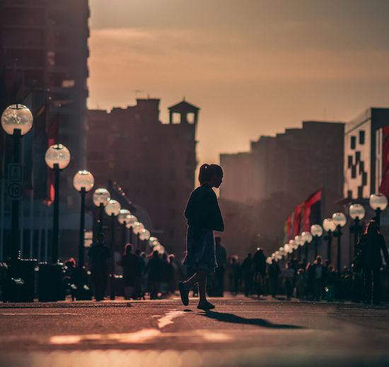 Man walking on street against sky during sunset