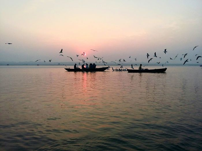 Famous sunrise of VARANASI Sunset Sea Outdoors Water Flying Cloud - Sky Sky Large Group Of Animals Nature Nautical Vessel Beauty In Nature Bird Flock Of Birds People First Eyeem Photo