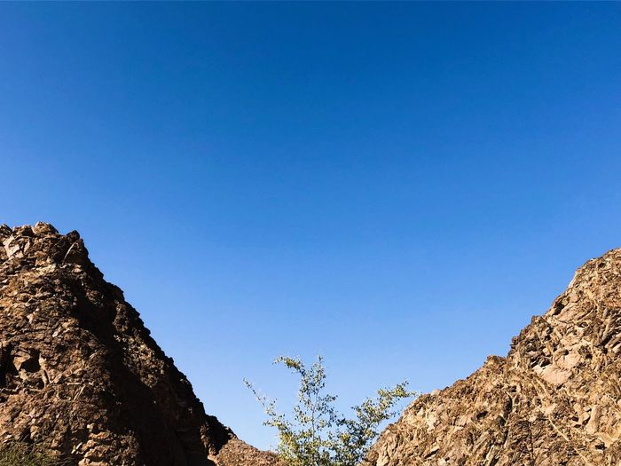 Sky Clear Sky Blue Low Angle View Copy Space Rock Nature Tree Solid Day No People Rock - Object Beauty In Nature Tranquility Scenics - Nature Tranquil Scene Rock Formation Mountain Sunlight Plant