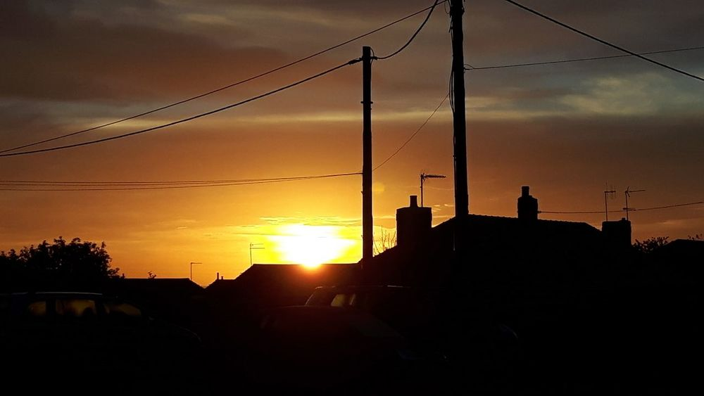 Sun rising over houses Sunrise Sun Buildings Shadow Village Houses Golf Club Sunset Silhouette Oil Pump City Sun Business Finance And Industry Water Dramatic Sky Sky Electricity Tower Electricity Pylon