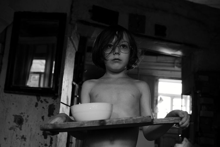 Shirtless boy holding food while standing at home