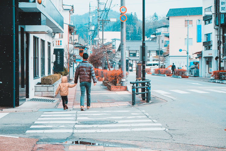 Father and son walked hand holding along the road. City Adult People Day Outdoors Lifestyles Men Walking Road Real People Rear View Street Japanese  Japan Kid Family Son Boy Father Hand Holding Warm Clothing Snow City Life Architecture Crosswalk Back Walk Love Cute City Street