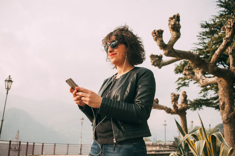 Smiling mid adult woman using phone standing against sky