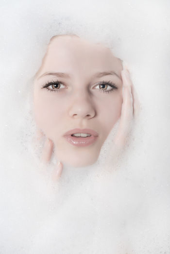 Portrait of woman amidst soap sud in bathtub