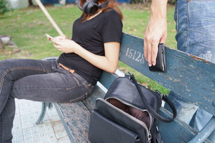 Midsection of man robbing wallet from bag while woman sitting on bench at park