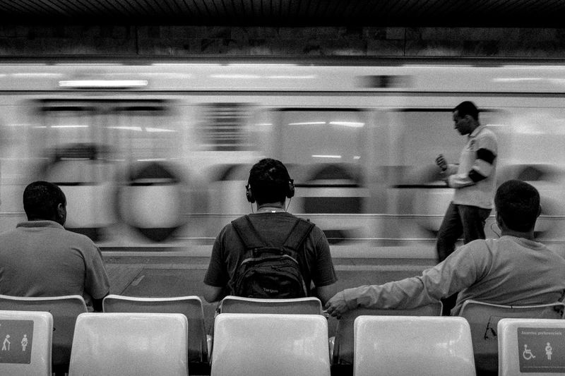 Rear View Of Men Sitting Against Blurred Motion Of Train At Subway Station