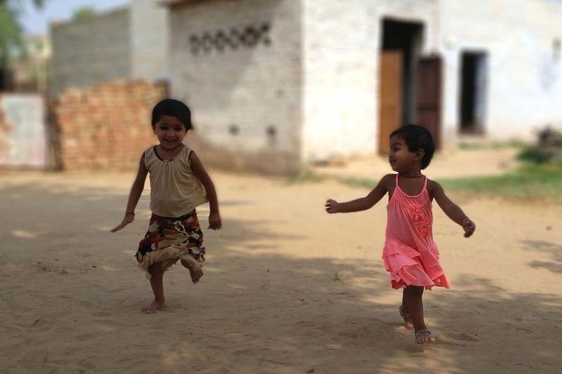 Full length of siblings running on sand