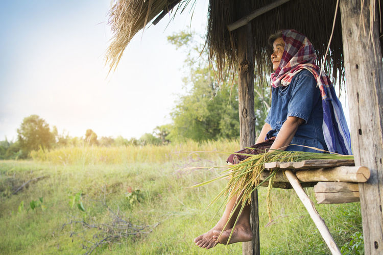 Senior Woman Sitting In Shed At Farm