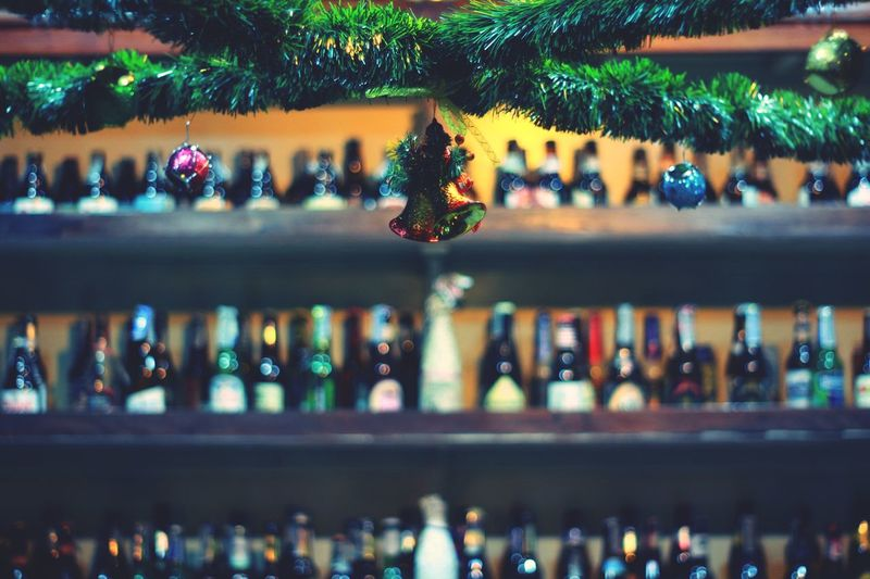Close-up of christmas decoration with bottles in background