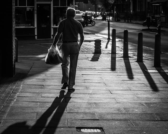 Rear view of woman walking with shopping bag on sidewalk in city
