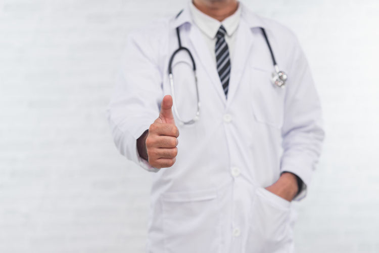 Midsection of doctor gesturing while standing against wall