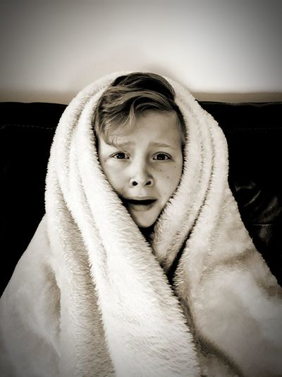 Portrait Of Scared Boy Wrapped In Blanket On Sofa