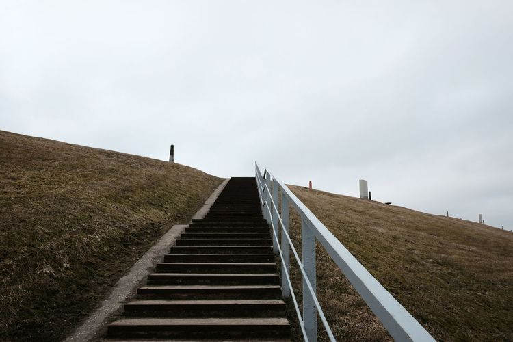 Low angle view of staircase on hill against sky