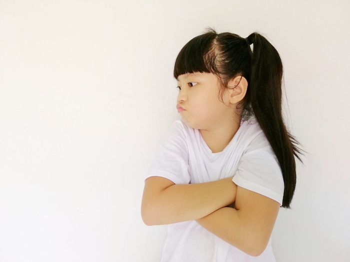 Side view of a girl looking away against white background